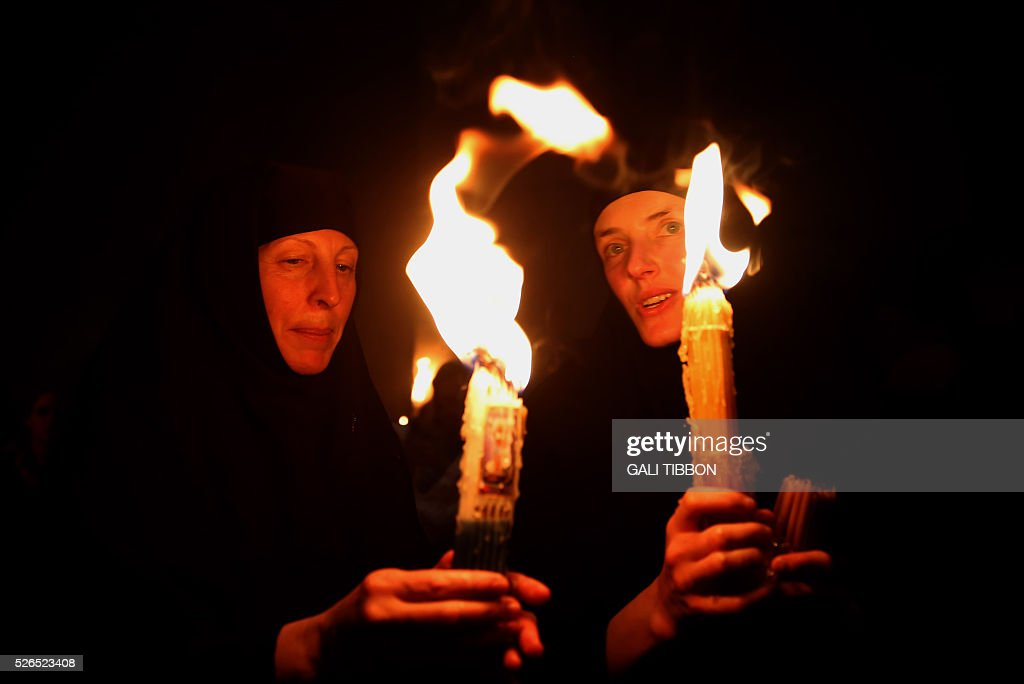 Russian Orthodox nuns hold candles lit from the 'Holy Fire' as thousands gather in the Church of the Holy Sepulchre in Jerusalem's Old City on April 30, 2016 during the Orthodox Easter ceremony. The ceremony celebrated in the same way for eleven centuries, is marked by the appearance of sacred fire in the two cavities on either side of the Holy Sepulchre. / AFP / GALI