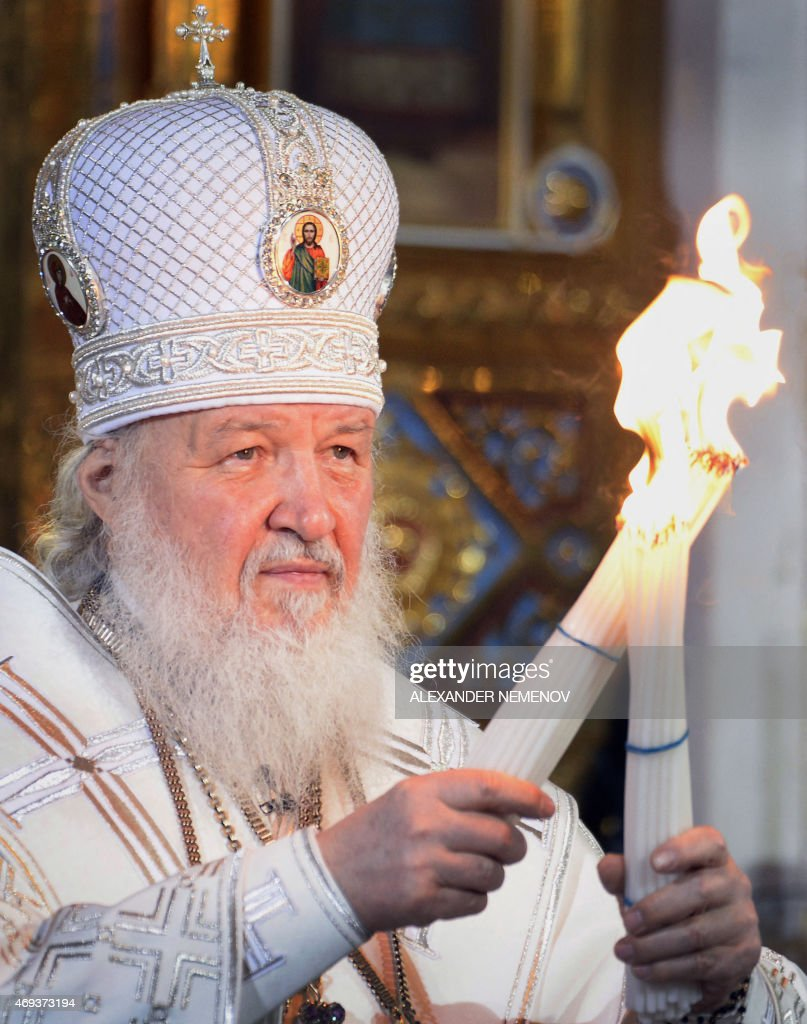 Russian Orthodox Patriarch Kirill holds candles representing the Holly Light with during an Orthodox Easter service in Moscow, early on April 12, 2015. AFP PHOTO / ALEXANDER NEMENOV