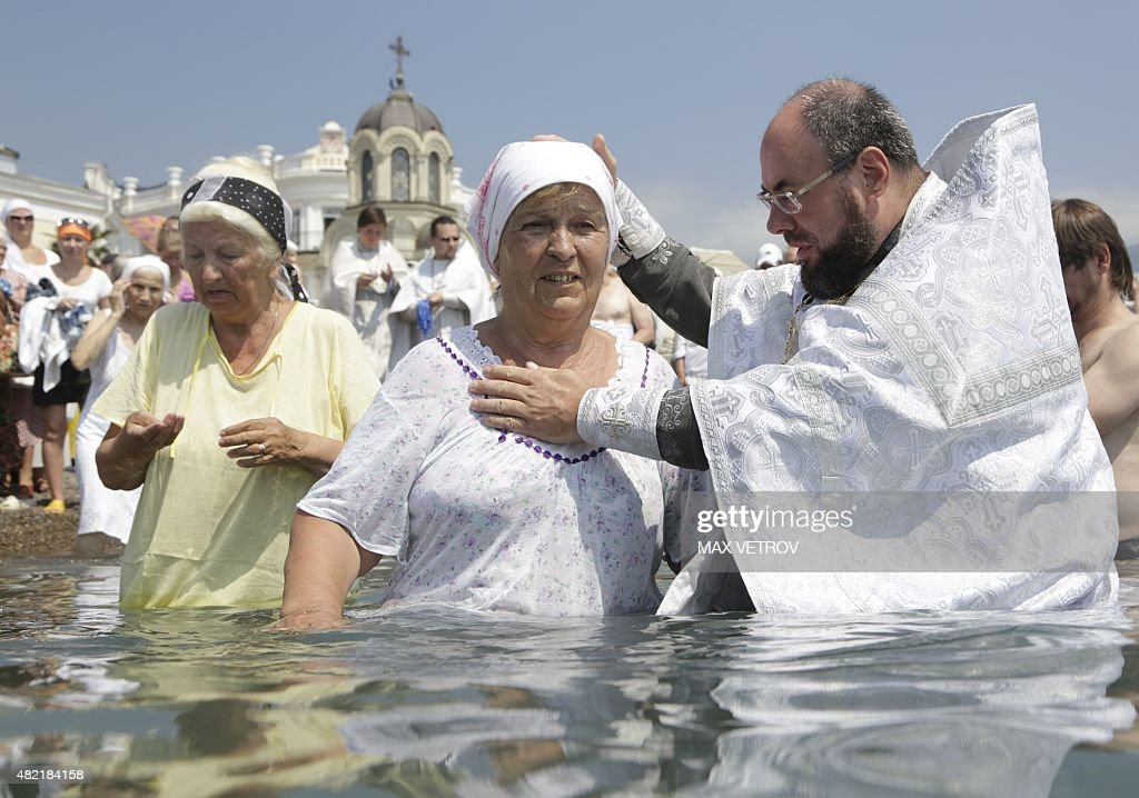 A Russian orthodox priest baptizes a woman in the Black Sea during a celebration of the 1000th anniversary of the Great Prince Vladimir canonization...