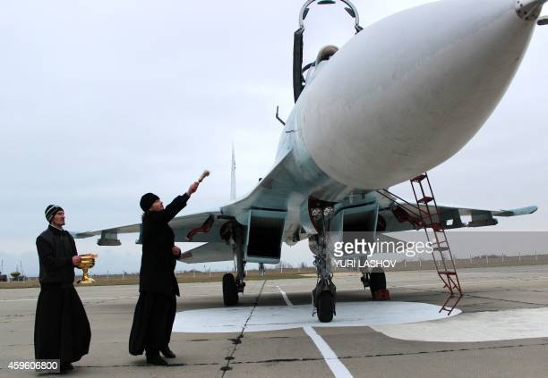 A Russian orthodox priest blesses a SU27 SM fighter jet on the airfield of Belbek military airport outside Sevastopol on November 26 2014 Crimean...