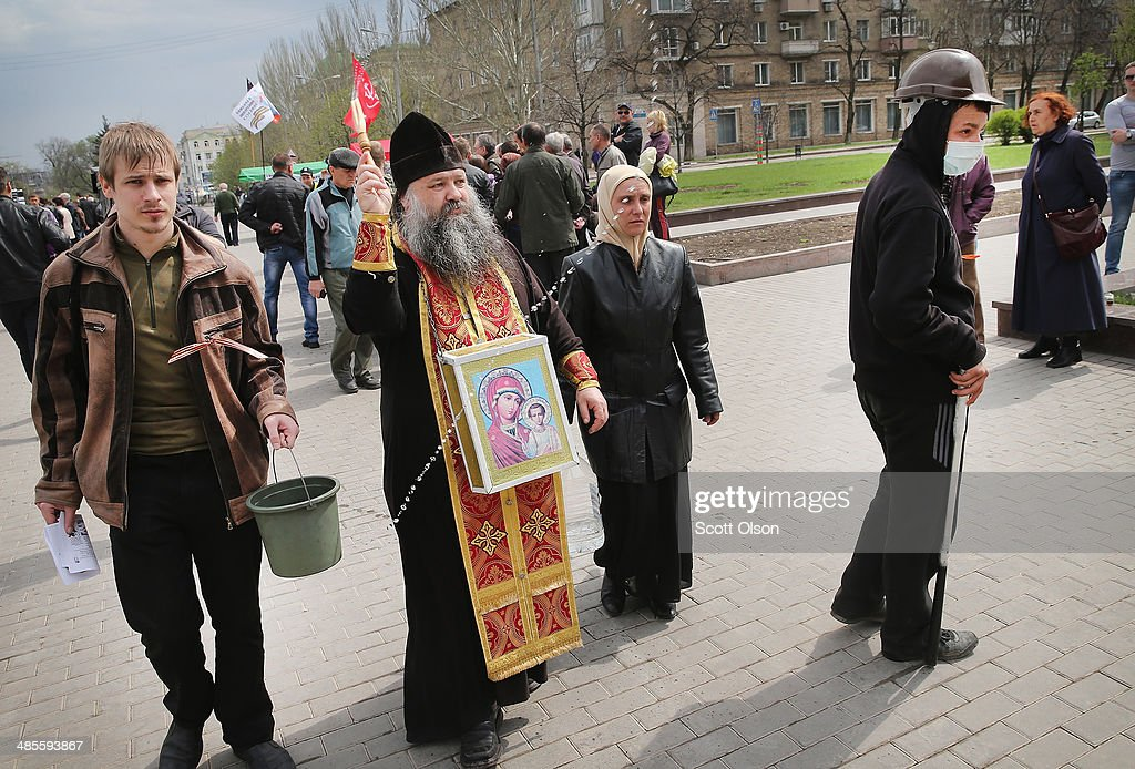 A Russian Orthodox priest blesses pro-Russian activists who are part of the occupying force inside the Donetsk Regional Administration building on April 19, 2014 in Donetsk, Ukraine. The group of activists who are occupying the building have surrounded it with a barricade of tires and barbed wire and are prepared to defend it with caches of Molotov cocktails strategically placed within the barricade. Activist leader, Denis Pushilin, who is co-head of the self-declared Donetsk People's Republic, said yesterday that they will not surrender until there is a change of leadership in Ukraine. Several bands of separatists, similar to those in Donetsk, have been occupying government buildings in other eastern Ukraine cities in recent weeks.