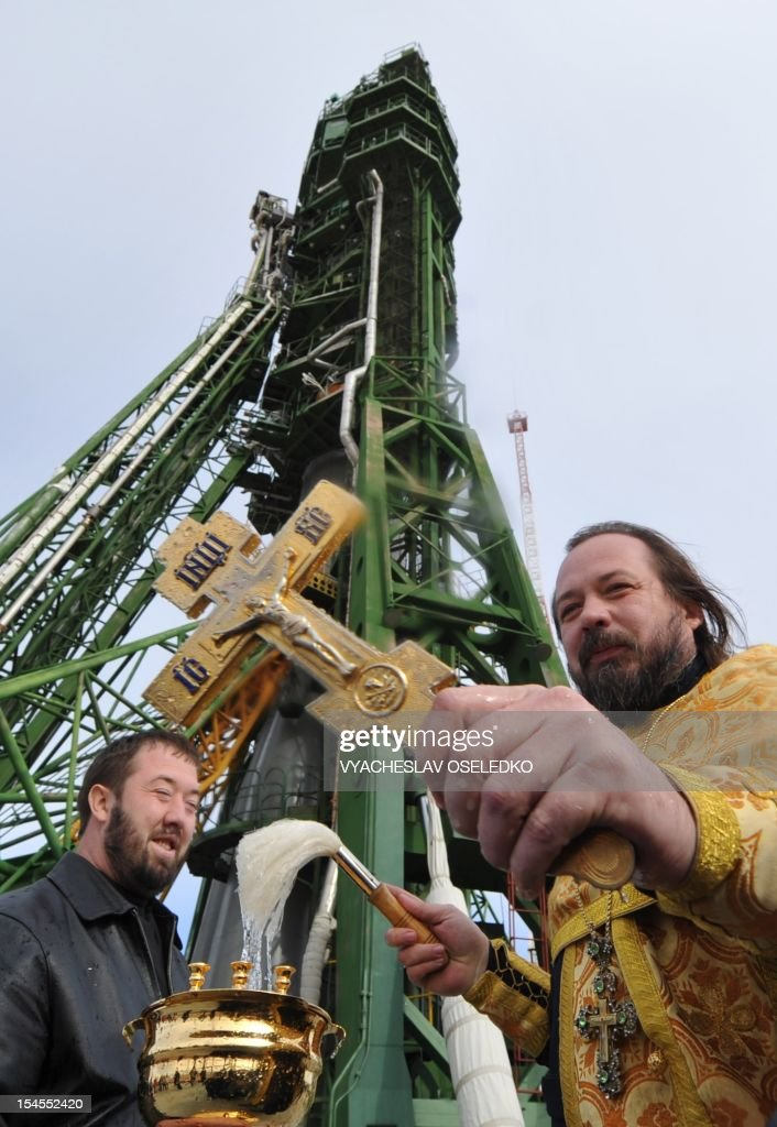 A Russian Orthodox priest blesses the Soyuz TMA-06M spacecraft of the next expedition to the International Space Station (ISS) at the launch pad of the Russian leased Kazakhstan's Baikonur cosmodrome, on October 22, 2012. The launch of the crew, including US astronaut Kevin Ford, Russian cosmonauts, Oleg Novitskiy and Evgeny Tarelkin, is scheduled for tomorrow.