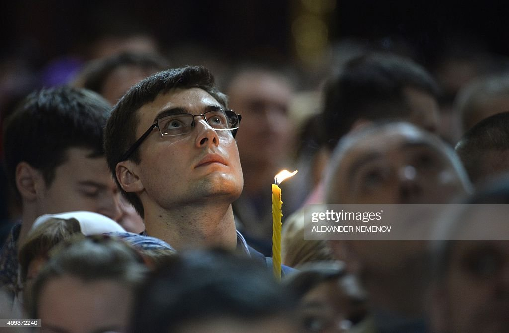 Russian Orthodox worshipers hold candles during an Orthodox Easter service in Moscow on April 11 2015 AFP PHOTO/ ALEXANDER NEMENOV