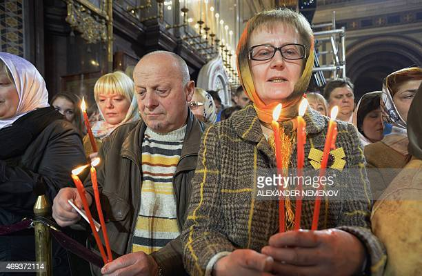 Russian Orthodox worshipers hold candles representing the Holly Light during an Orthodox Easter service in Moscow on April 11 2015 AFP PHOTO/...
