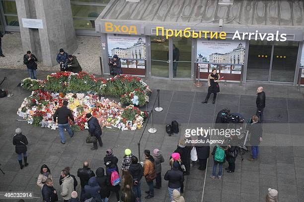 Russian people lay flowers toys and light candles to commemorate Russian plane crash victims at Pulkovo airport in SaintPetersburg Russia on November...