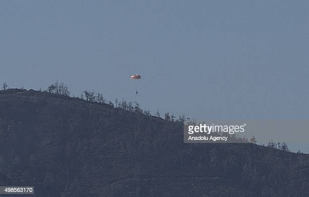 Russian pilot parachutes out of a warplane which went down in Syria's northwestern Turkmen town of Bayirbucak near Turkeys border on November 24 2015
