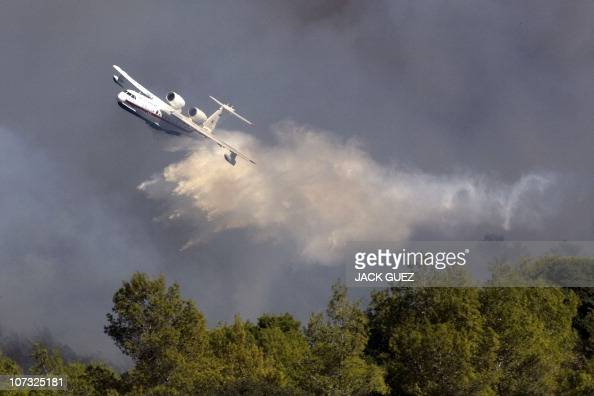 A Russian plane sprays its load of water over flames in the Carmel Forest in the outskirts of Haifa on December 4 2010 as thousands of Israeli...