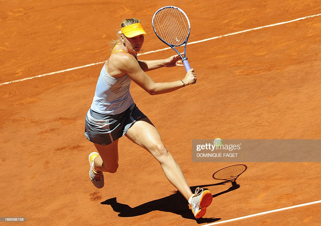Russian player Maria Sharapova returns the ball to US player Serena Williams during their women's singles final tennis match at the Madrid Masters at the Magic Box (Caja Magica) sports complex in Madrid on May 12, 2013. AFP PHOTO / DOMINIQUE FAGET