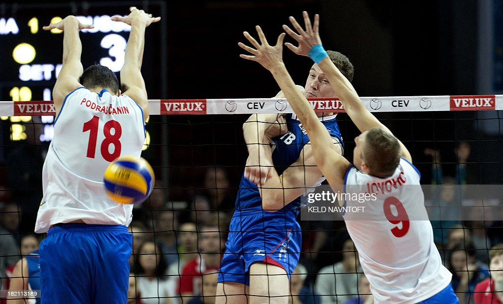 Russian player Sergey Grankin spikes a ball against Serbian players Marko Podrascanin and Nikola Jovovic during the semifinal match between Serbia...