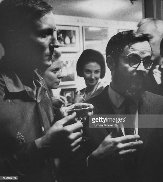 Russian poet Evgeny Evtushenko standing at a party with interpreter Edward Keenan