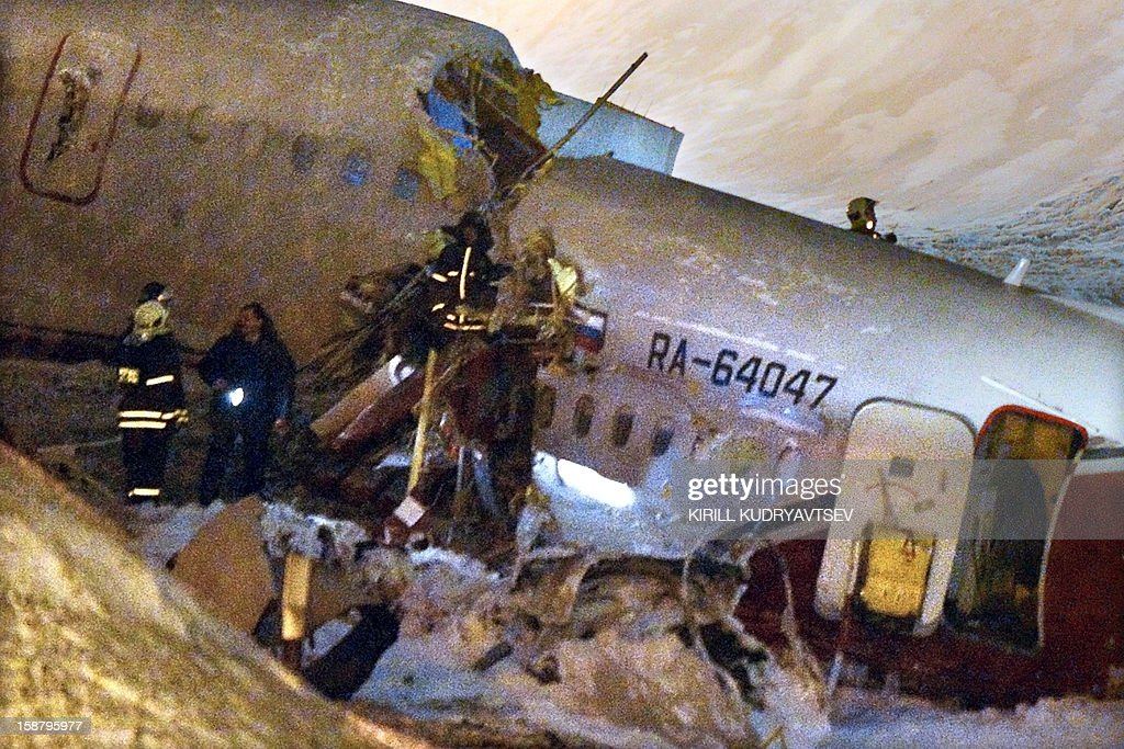Russian police investigators and emergency services teams work at the Tu-204 jet crash site near the Vnukovo airport outside Moscow on December 29, 2012. Four people were killed and four were injured when a Russian-made airliner overshot a runway on landing at a Moscow airport and crashed onto a nearby highway, officials said. AFP PHOTO / KIRILL KUDRYAVTSEV