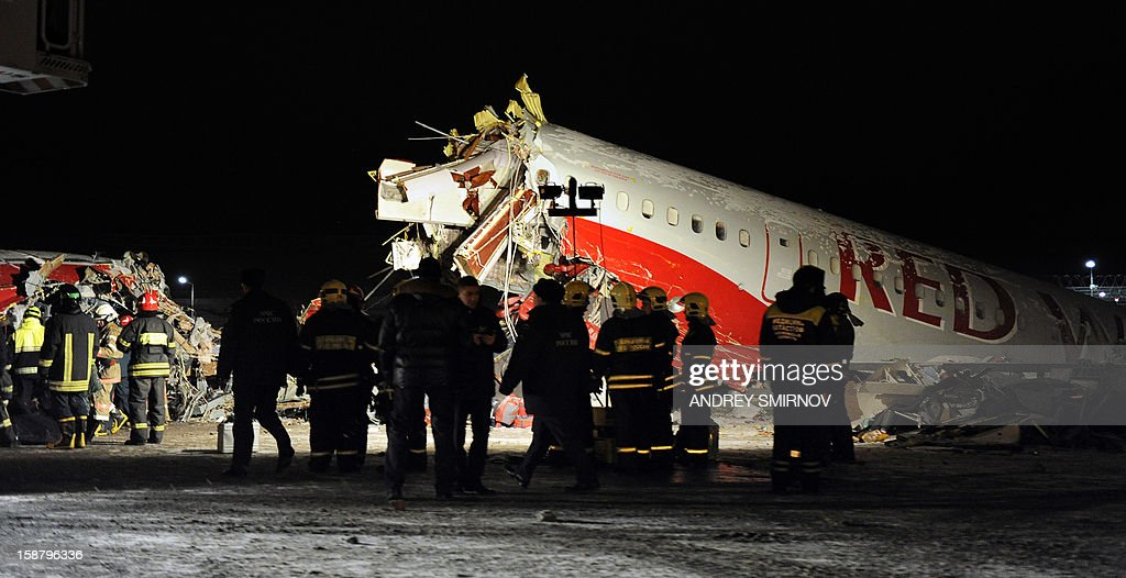 Russian police investigators and emergency services teams work at the Tu-204 jet crash site near the Vnukovo airport outside Moscow on December 29, 2012. Four people were killed and four were injured when a Russian-made airliner overshot a runway on landing at a Moscow airport and crashed onto a nearby highway, officials said. AFP PHOTO / ANDREY SMIRNOV