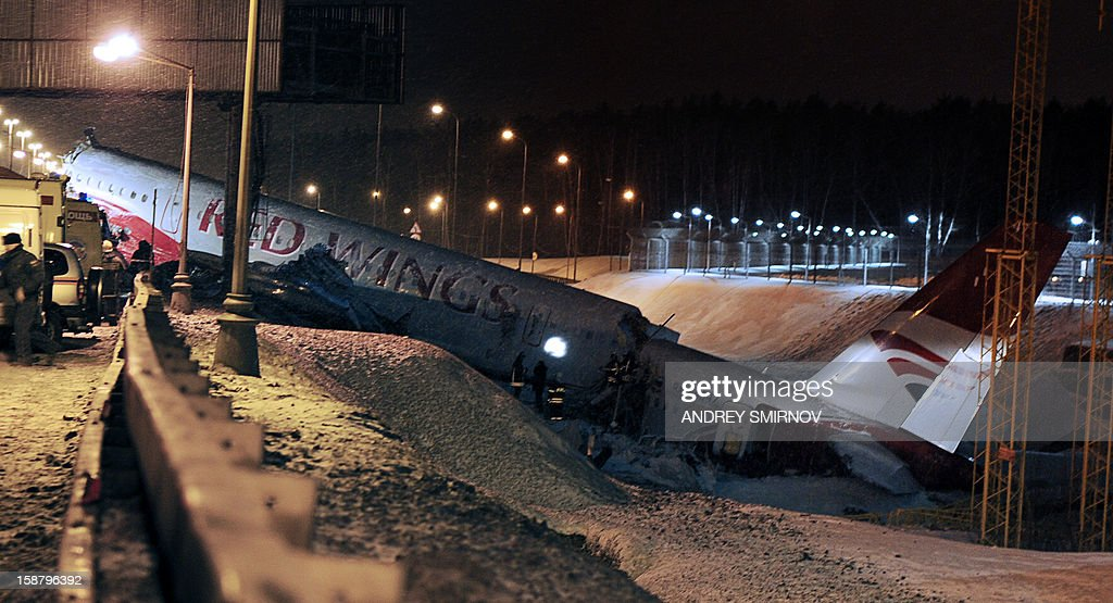 Russian police investigators and emergency services teams work at the Tu-204 jet crash site near the Vnukovo airport outside Moscow on December 29, 2012. Four people were killed and four were injured when a Russian-made airliner overshot a runway on landing at a Moscow airport and crashed onto a nearby highway, officials said.