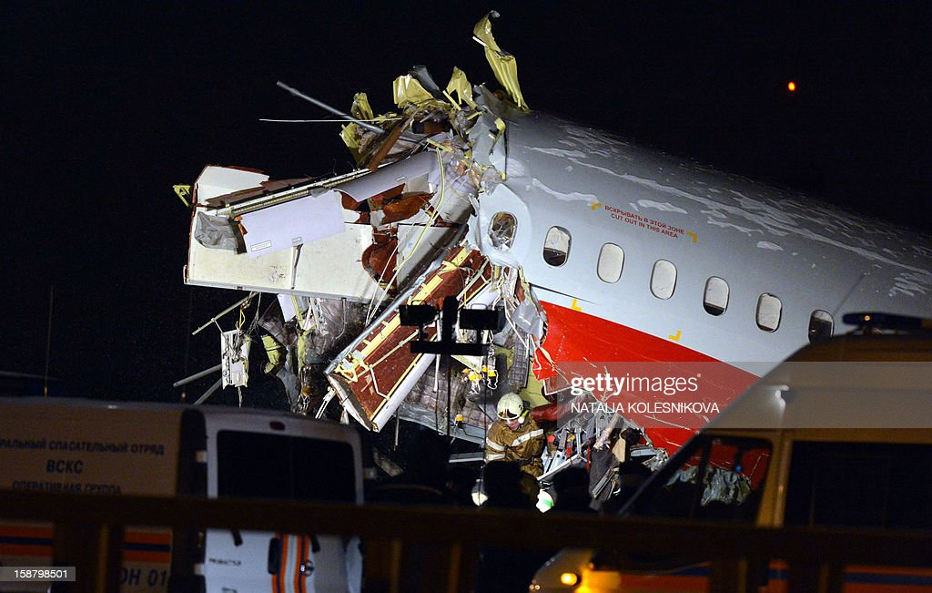 Russian police investigators and emergency services teams work at the Tu-204 jet crash site near Moscow on December 29, 2012. Four crew were killed when a Russian airliner crashed into a motorway and broke up into three pieces after overshooting the runway at an international Moscow airport. The Red Wings airlines Russian-made Tu-204 jet -- empty of passengers and carrying just its eight crew on a return trip from the Czech Republic -- caught fire after crashing through the perimeter fence of Vnukovo airport in the west of the city.