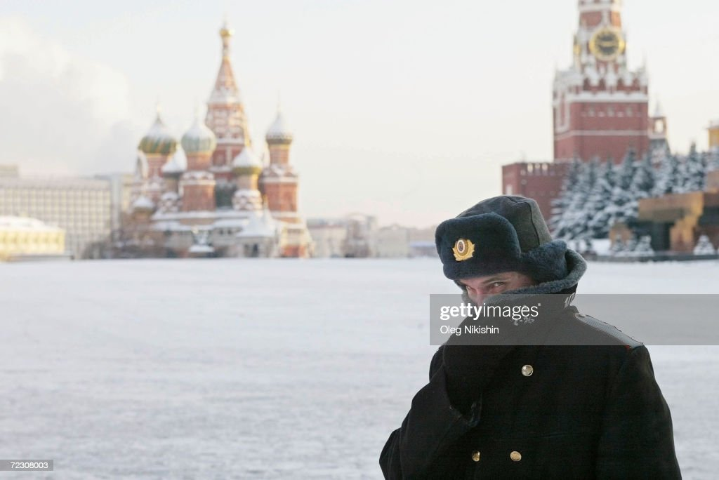 Russian police officer braving the bitter cold patrols Red Square with the Kremlin in the background January 7 2003 in Moscow Temperatures fell to 27...