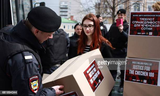Russian police officer holds a boxes alledgedly containing signed petitions calling for a probe into a reported crackdown on Chechnya's LGBT...