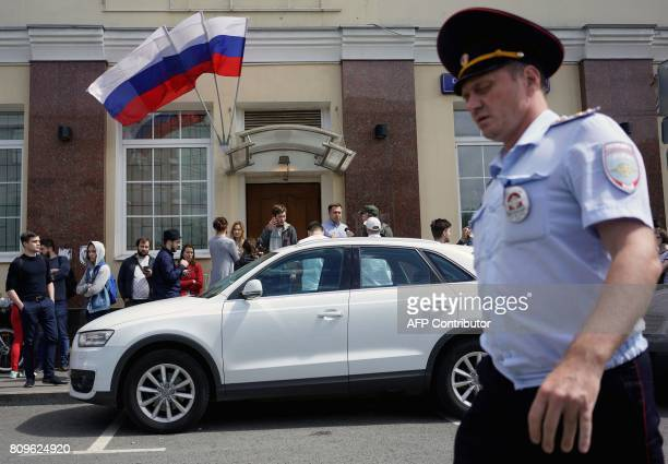 A Russian police officer passes by the campaign headquarters of Russian opposition leader Alexei Navalny on July 6 in Moscow Russian police were...