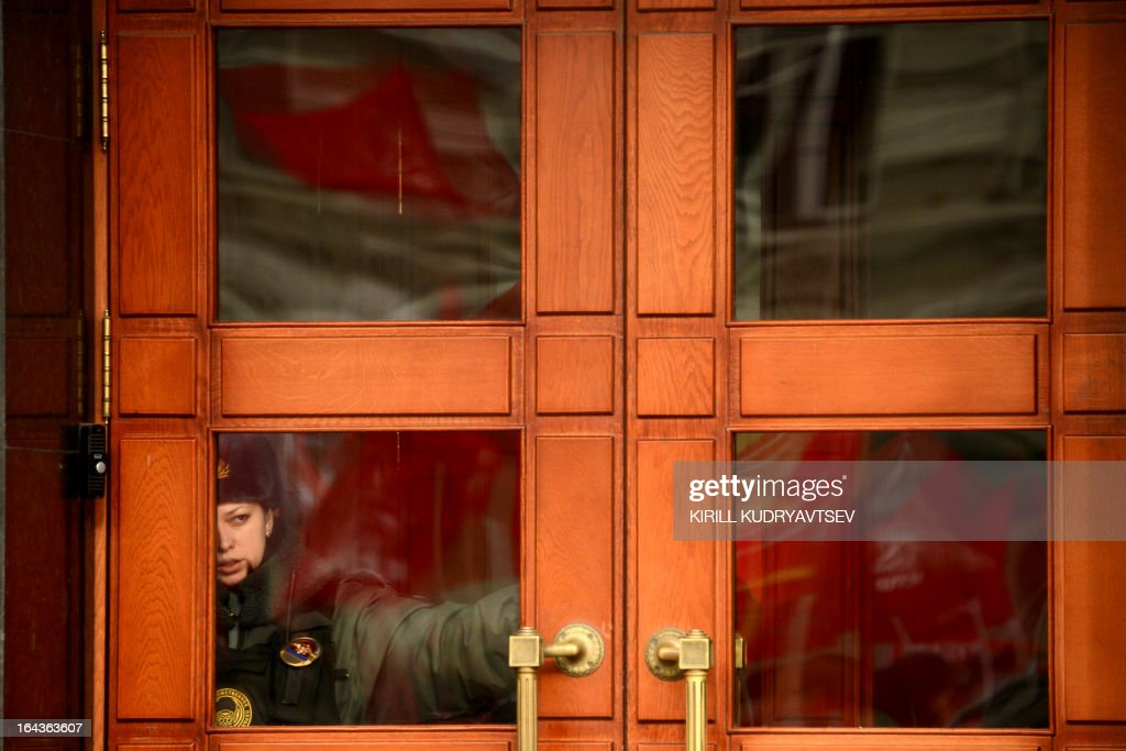 A Russian police officer stands guard as supporters of the Russian Communist Party are reflected in the window during a rally against rising utility bills in Moscow on March 23, 2013.