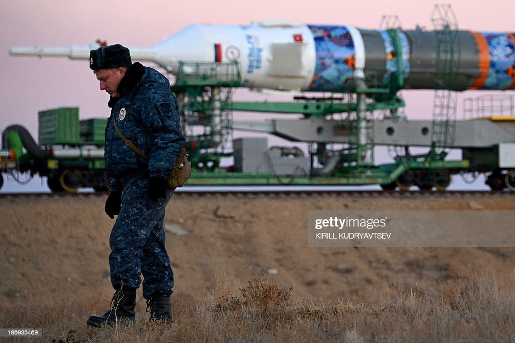 A Russian police officer stands guard while the Soyuz-FG launch vehicle with Soyuz TMA-11M spacecraft of the International Space Station (ISS) Expedition 39 aboard is transported to a launch pad in the Russian-leased Baikonur cosmodrome in Kazakhstan, on November 5, 2013. The Soyuz TMA-11M with an international crew, including Japanese astronaut Koichi Wakata, Russian cosmonaut Mikhail Tyurin and US astronaut Rick Mastracchio, and with an unlit torch of Sochi 2014 Winter Olympic aboard is scheduled to blast off to the ISS from Baikonur on November 7. The torch is scheduled to return back to Earth on November 11.