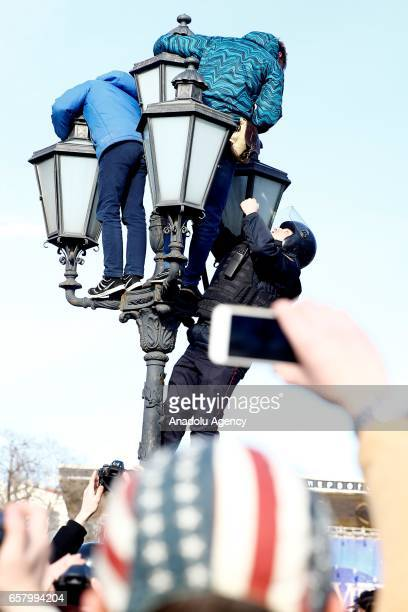 Russian police officers climbs on a lamppost to detain protesters during an opposition rally on March 26 2017 in Moscow