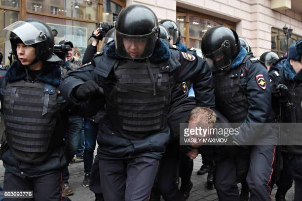 TOPSHOT Russian police officers detain a man in central Moscow on April 2 as Russian opposition promised protests after police detained hundreds of...