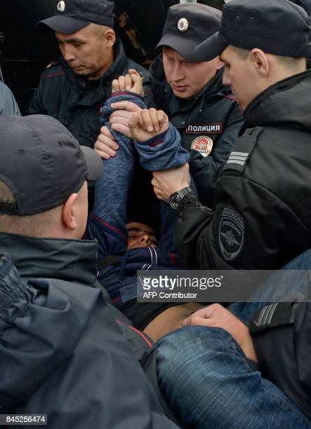 Russian police officers detain a participant during an unauthorized rally in Dvortsovaya Square in central Saint Petersburg on September 10 in...