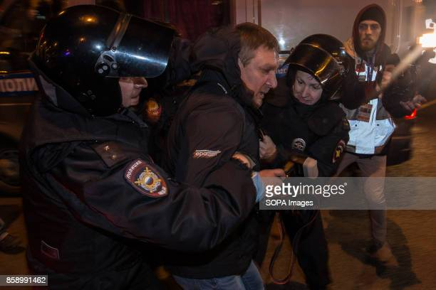 Russian police officers detain a photographer during an unauthorized opposition rally The President of Russia Vladimir Putin celebrated his 65th...