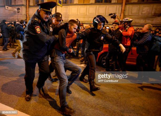 TOPSHOT Russian police officers detain a supporter of opposition leader Alexei Navalny during an unauthorized rally in Saint Petersburg on October 7...