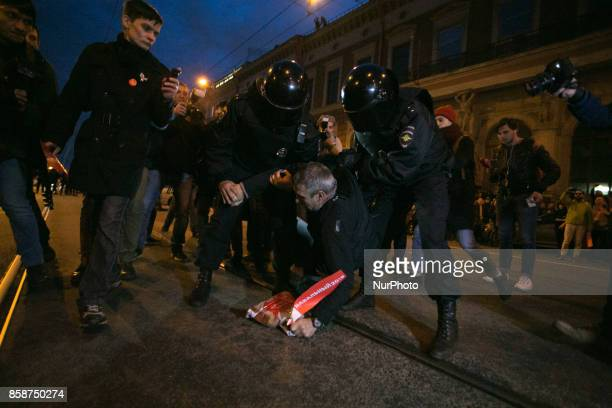 Russian police officers detain a supporter of opposition leader Alexei Navalny during an unauthorized rally in Saint Petersburg on October 7 2017...