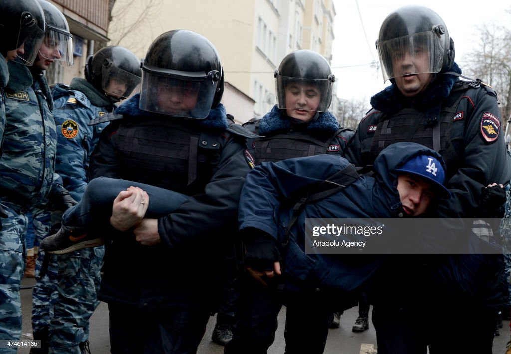 Russian police officers detain an opposition activist outside a court room during the ''Bolotnaya'' trial in Moscow, Russia on February 24, 2014. A Moscow judge on February 21, 2014, convicted eight anti-government protesters of rioting during a 2012 protest against Vladimir Putin.