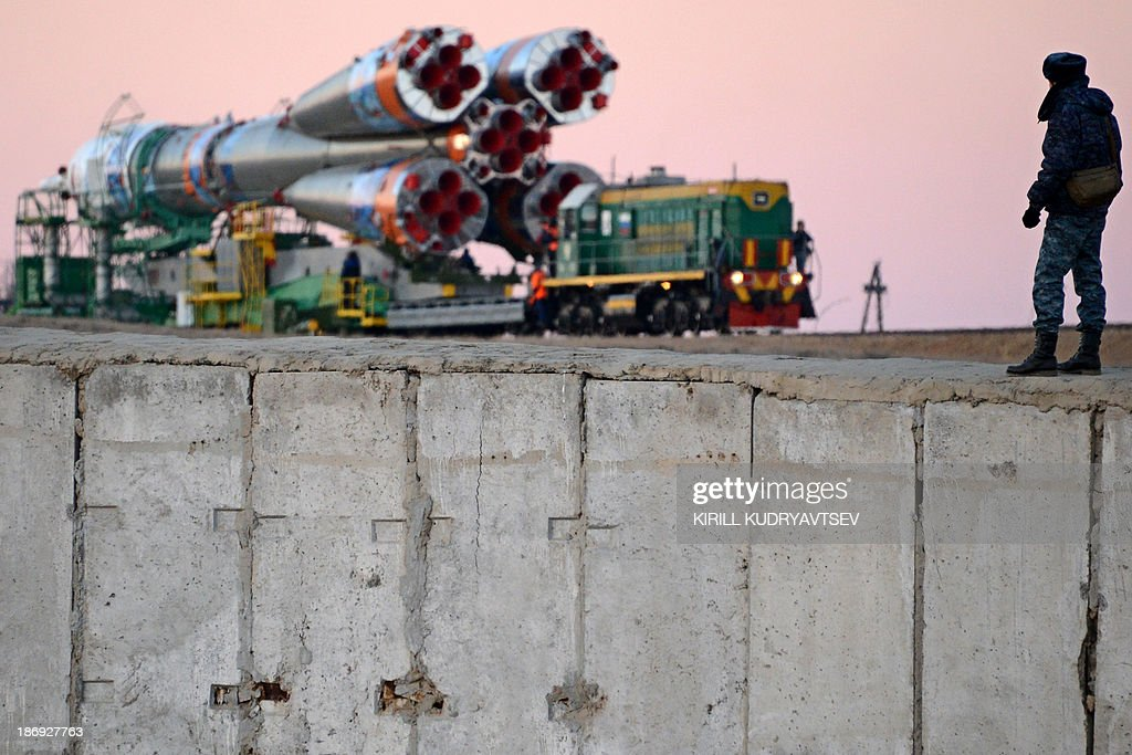 A Russian police officers stands guard while the Soyuz-FG launch vehicle with Soyuz TMA-11M spacecraft of the International Space Station (ISS) Expedition 39 aboard is transported to a launch pad in the Russian-leased Baikonur cosmodrome in Kazakhstan, on November 5, 2013. The Soyuz TMA-11M with an international crew, including Japanese astronaut Koichi Wakata, Russian cosmonaut Mikhail Tyurin and US astronaut Rick Mastracchio, and with an unlit torch of Sochi 2014 Winter Olympic aboard is scheduled to blast off to the ISS from Baikonur on November 7. The torch is scheduled to return back to Earth on November 11.