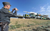 A Russian policeman takes photos the Souyz TMA04M rocket of the International Space Station during its transportation to a launch pad in the Russian...