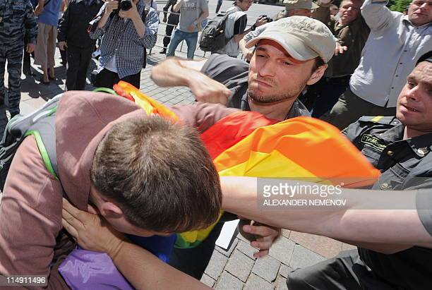 A Russian policeman tries to stop a man hitting a gay rights activist on their attempt to hold an unauthorized rally in central Moscow on May 28 2010...