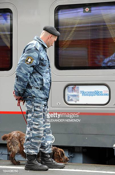 A Russian policemen and his dog examine a new luxury train running between Moscow and Nice prior its departure at Moscow's Belorussky station on...