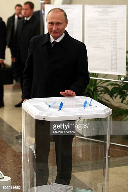 Russian Preisdent Vladimir Putin holds a ballot paper as he votes at a polling station on September 18 2016 in Moscow Russia Legislative...