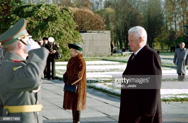 Russian President Boris Yeltsin and Britain's Queen Elizabeth II walk past the guard of honour and a Sovietstyle flag during a ceremony at the...