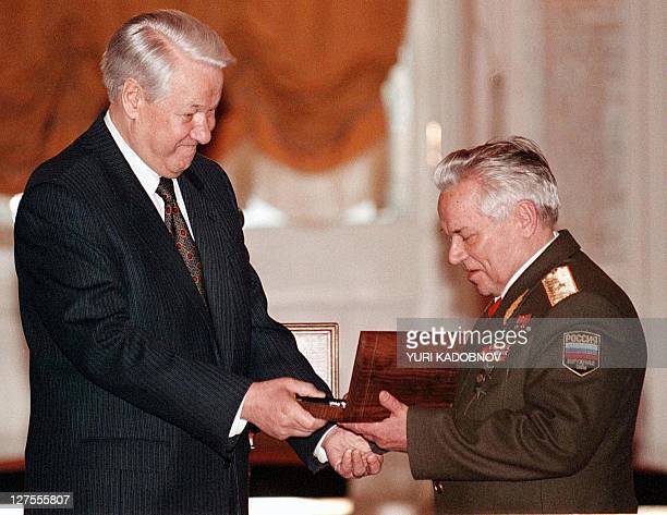 Russian President Boris Yeltsin hands to General Mikhail Kalashnikov a weapon in a special presentation box that bears the name of the renowned arms...