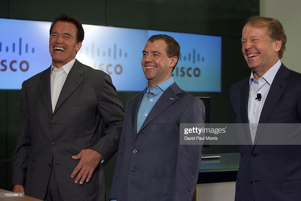 Russian President <a gi-track='captionPersonalityLinkClicked' href=/galleries/search?phrase=Dmitry+Medvedev&family=editorial&specificpeople=554704 ng-click='$event.stopPropagation()'>Dmitry Medvedev</a> (C) laughs with Cisco Chairman and CEO <a gi-track='captionPersonalityLinkClicked' href=/galleries/search?phrase=John+Chambers&family=editorial&specificpeople=677131 ng-click='$event.stopPropagation()'>John Chambers</a> (R) and California Gov. <a gi-track='captionPersonalityLinkClicked' href=/galleries/search?phrase=Arnold+Schwarzenegger&family=editorial&specificpeople=156406 ng-click='$event.stopPropagation()'>Arnold Schwarzenegger</a> during a demonstration at Cisco headquarters June 23, 2010 in San Jose, California. During the meeting Cisco Chairman and CEO <a gi-track='captionPersonalityLinkClicked' href=/galleries/search?phrase=John+Chambers&family=editorial&specificpeople=677131 ng-click='$event.stopPropagation()'>John Chambers</a> signed a Memorandum of Understanding with President of Renova Group Viktor Vekselberg extending its existing venture commitment to Russia's innovation economy with an incremental US$100 million to the Skolkovo Project.
