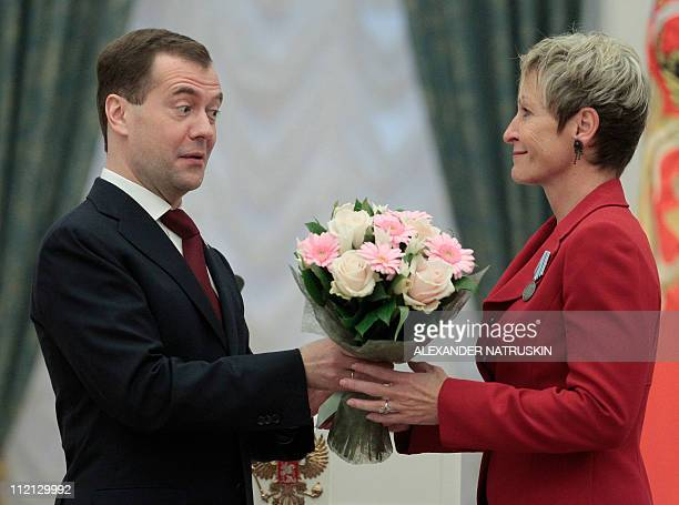 "Russian President Dmitry Medvedev presents flowers to US astronaut Peggy Whitson who received medal ""For Merits in Space Exploration"" during an..."