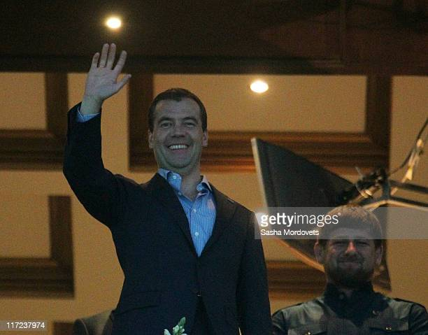 Russian President Dmitry Medvedev waves as Chechnya's President Ramzan Kadyrov looks on during the Presidential Cup races June 24 2011 in Kazan Russia