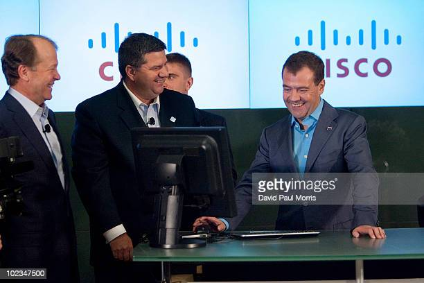 Russian President Dmitry Medvedev works on the computer as Cisco Chairman and CEO John Chambers and Jim Grubb Chief Demonstration Officer watch at...