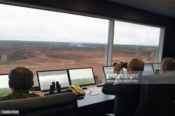 TOPSHOT Russian President Vladimir Putin accompanied by Defence Minister Sergei Shoigu uses a pair of binoculars as he inspects the joint Zapad2017...