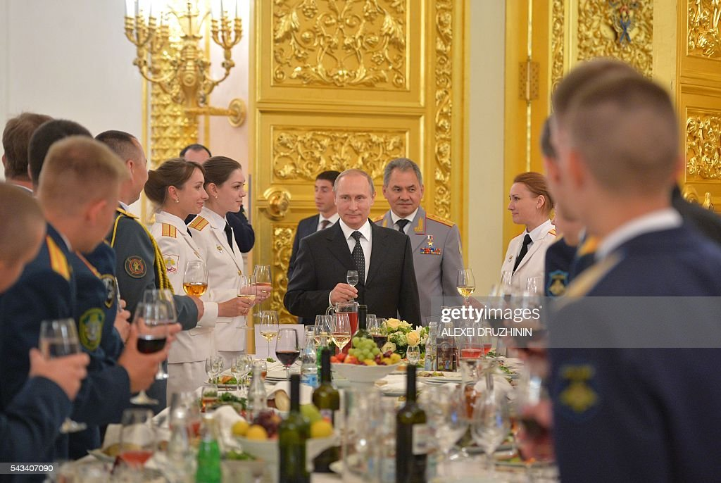 Russian President Vladimir Putin (C), accompanied by Defence Minister Sergei Shoigu, toasts with graduates of military academies during a reception at the Kremlin in Moscow on June 28, 2016. / AFP / SPUTNIK / ALEXEI