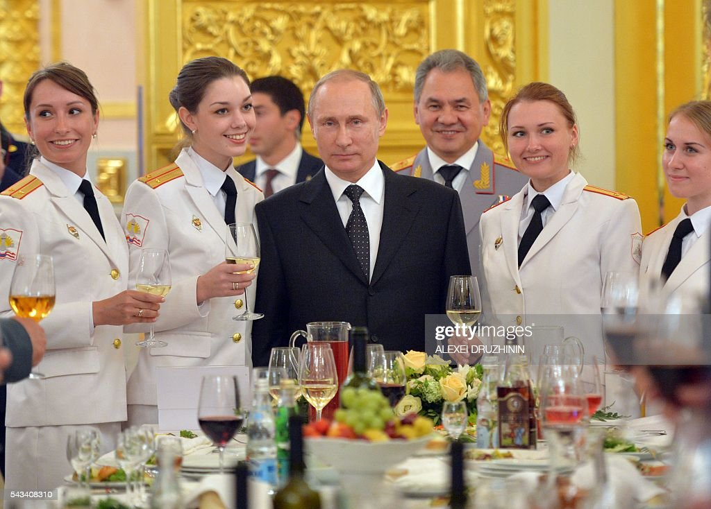 Russian President Vladimir Putin (C), accompanied by Defence Minister Sergei Shoigu, poses for photographs with graduates of military academies during a reception at the Kremlin in Moscow on June 28, 2016. / AFP / SPUTNIK / ALEXEI