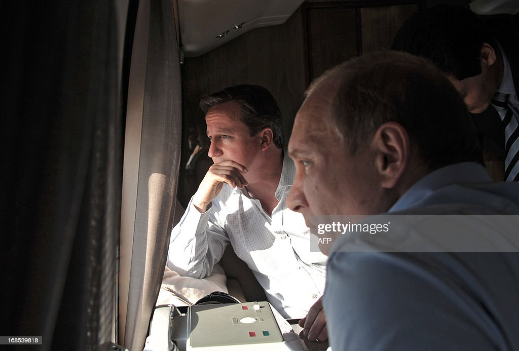 Russian President Vladimir Putin (R) and Britain's Prime Minister David Cameron look out the windows as they fly by helicopter to inspect the 2014 Winter Olympic facilities after their meeting at the Bocharov Ruchei state residence in Sochi on May 10, 2013. Britain and Russia on May 10 sought to forge a joint approach to the crisis in Syria, as US Secretary of State John Kerry said there was 'strong evidence' Damascus had used chemical weapons against rebels.
