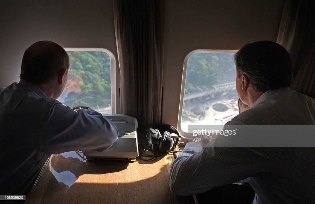 Russian President Vladimir Putin (L) and Britain's Prime Minister David Cameron look out the windows as they fly by helicopter to inspect the 2014 Winter Olympic facilities after their meeting at the Bocharov Ruchei state residence in Sochi on May 10, 2013. Britain and Russia on May 10 sought to forge a joint approach to the crisis in Syria, as US Secretary of State John Kerry said there was 'strong evidence' Damascus had used chemical weapons against rebels. AFP PHOTO / RIA NOVOSTI / PRESDIENTIAL PRESS SERVICE / ALEXEY NIKOLSKY