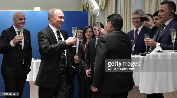 Russian President Vladimir Putin and FIFA president Gianni Infantino meet with football legends draw assistants and other attendees ahead of the...