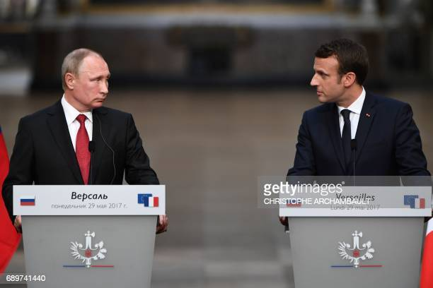 Russian President Vladimir Putin and French President Emmanuel Macron look at each other during a joint press conference in the Galerie des Batailles...