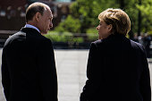 Russian President Vladimir Putin and German Chancellor Angela Merkel attend a wreath laying ceremony at the Unknown Soldiers's Tomb on May 10 2015 in...