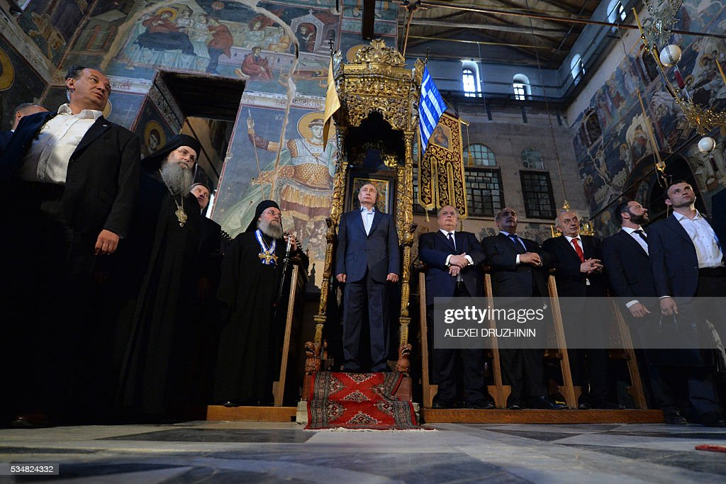 Russian President Vladimir Putin (C) and Greek Foreign Minister Nikos Kotzias (R) stand during a visit to the monastic community of Mount Athos, in Karyes on May 28, 2016. Putin, who has often talked about his strong Orthodox faith, will join celebrations for the 1,000th anniversary of the Russian presence at the ancient, all-male monastic community of Mount Athos. The visit, Putin's first to the EU since December, comes at a low ebb in relations between Russia and Europe over the conflict in Ukraine that broke out in 2014, with sanctions still in force against Moscow. / AFP / POOL / Alexei Druzhinin